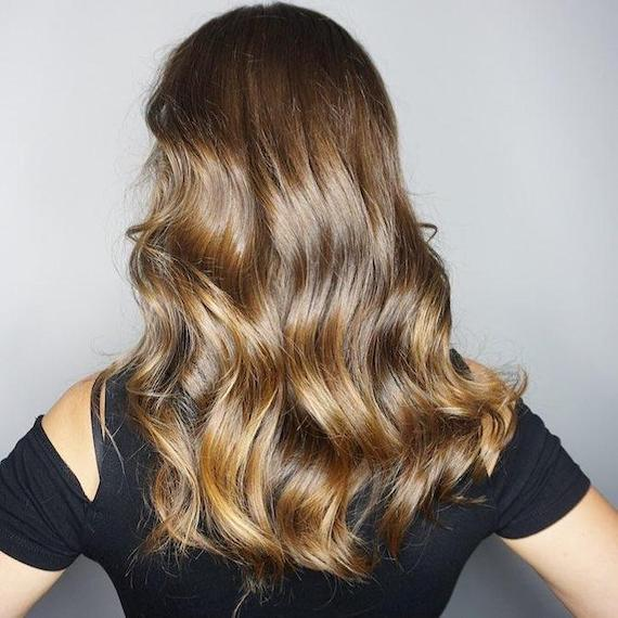 Back of woman's head with long, wavy, glossy brunette hair, created using Wella Professionals.