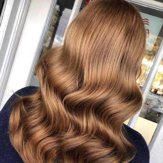 Back of woman's head with glossy, chestnut brown hair, created using Wella Professionals.