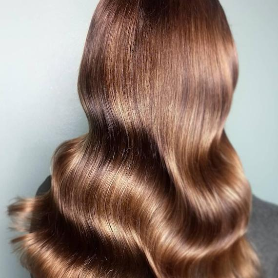 Back of woman's head with long, wavy, glossy caramel brown hair, created using Wella Professionals.