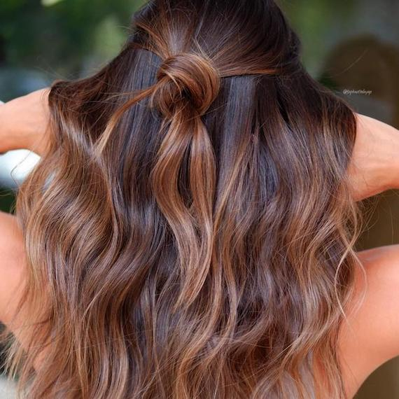 Back of woman's head with wavy hair and a toffee balayage, created using Wella Professionals.