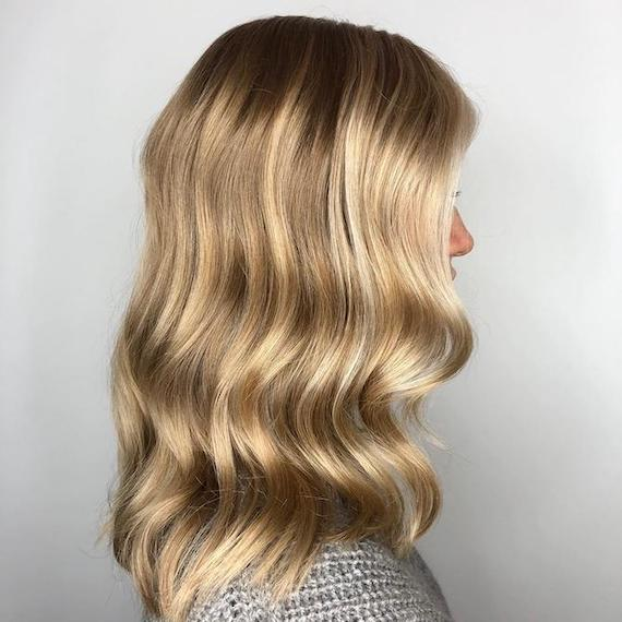 Side profile of woman with a root shadow and blonde babylights, created using Wella Professionals.