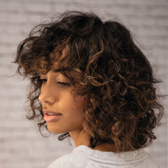 Side profile of woman with golden twilighting through dark curly hair, created using Wella Professionals.