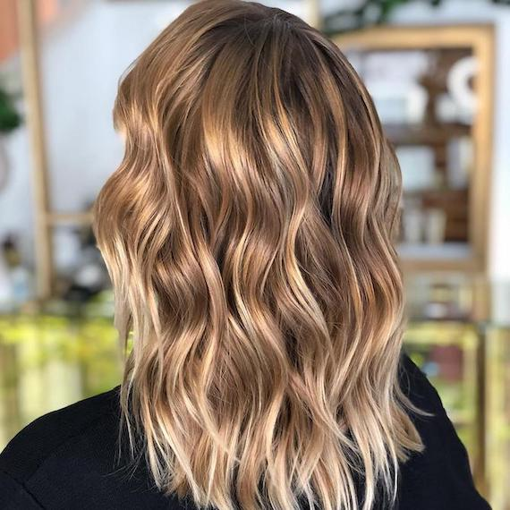 Back of woman's head with blonde hair and brunette lowlights, created using Wella Professionals.
