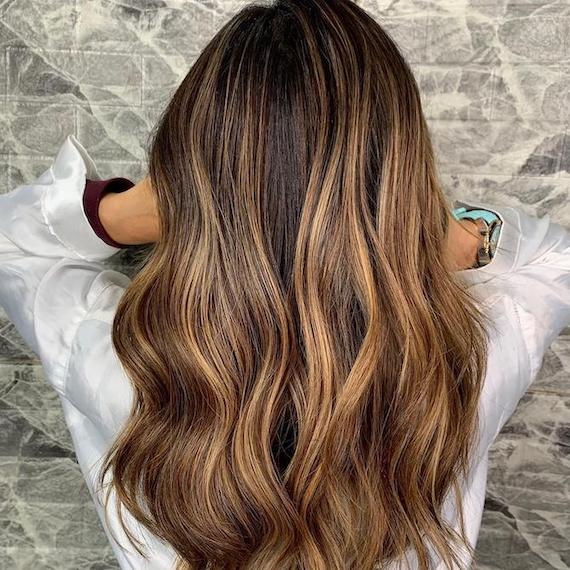 Back of woman's head with wavy, mid-length, brown hair and chunky caramel balayage, created using Wella Professionals.