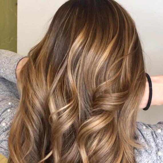 Back of woman's head with brown hair and a light caramel blonde balayage, created using Wella Professionals.