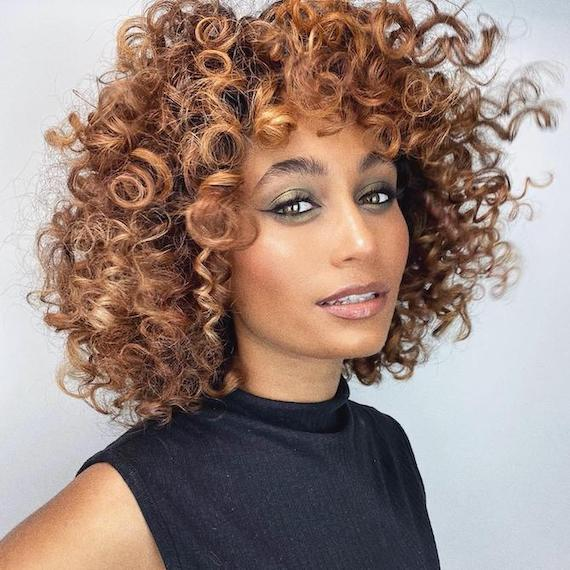 Woman facing the camera with brown, curly hair and caramel balayage, created using Wella Professionals.