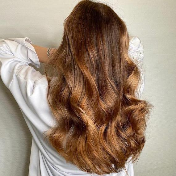 Back of woman's head with long, loosely curled, brown hair and caramel balayage, created using Wella Professionals.