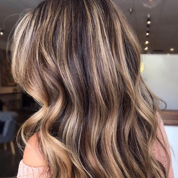 Back of woman's head with long, wavy hair and caramel blonde highlights, created using Wella Professionals.