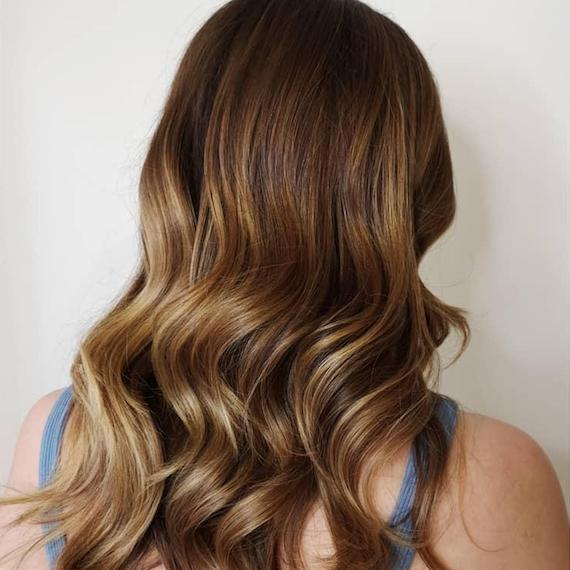 Back of woman's head with long, loosely curled hair and caramel blonde balayage, created using Wella Professionals.