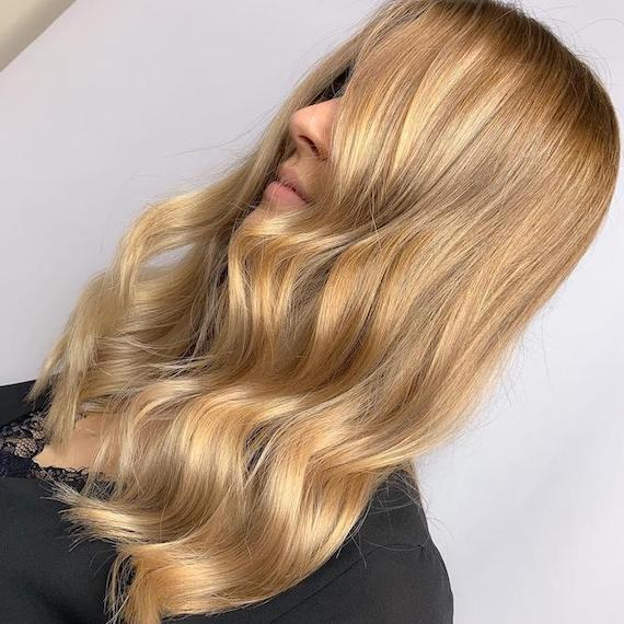 Side profile of woman with bright blonde hair and caramel highlights, created using Wella Professionals.