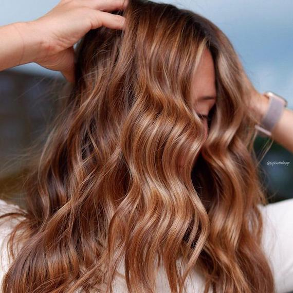 Photo of woman with long, wavy, light brown hair that features caramel and blonde highlights. Color created using Wella Professionals.