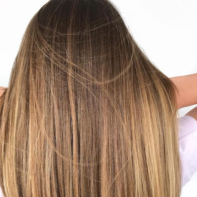 Back of woman's head with long, straight dark blonde hair and caramel highlights, created using Wella Professionals.