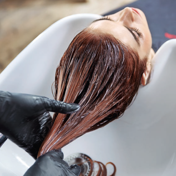 Photo of a woman having her hair washed by a hairdresser over a backwash sink.