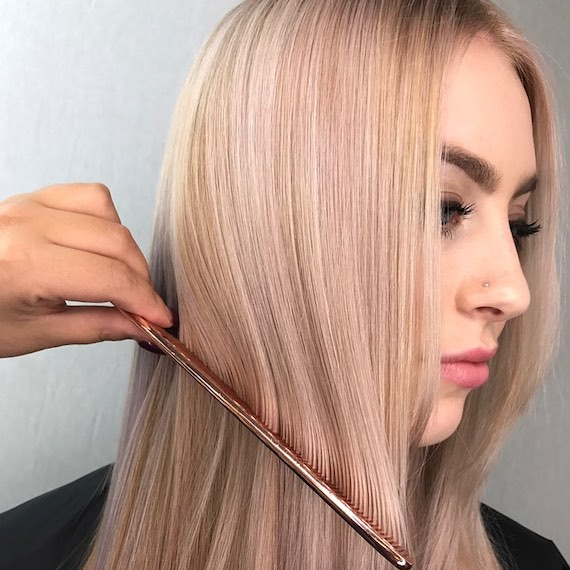 Photo of blonde woman having her long, straight hair combed, created using Wella Professionals.