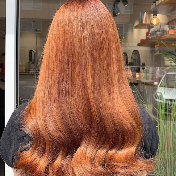 Photo of the back of a woman's head with red hair styled in a bouncy blowdry style.