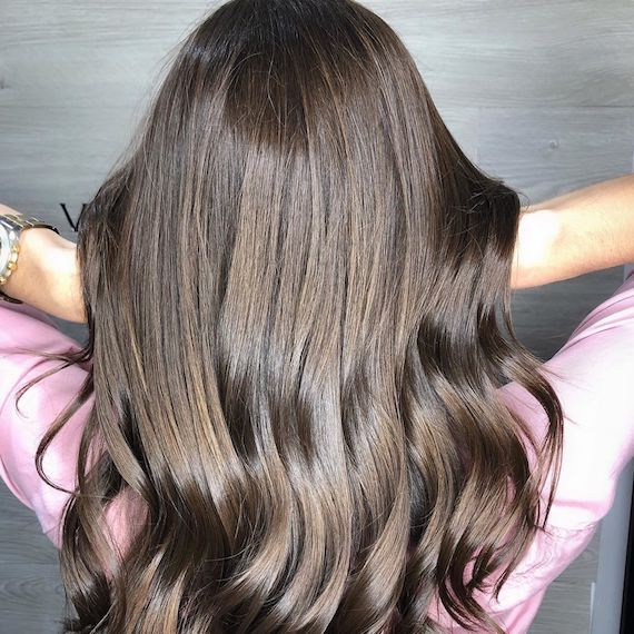 Image of the back of a woman's head, showing super-shiny brunette hair styled in loose waves.
