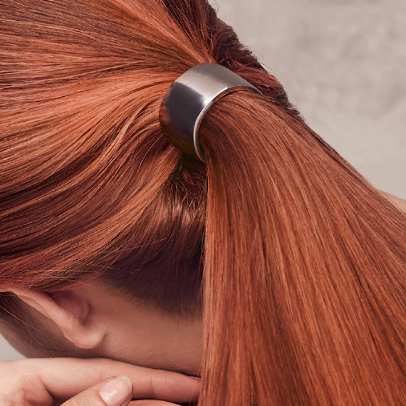 Image of the back of a woman's head, showing vibrant red hair fixed into a low ponytail.