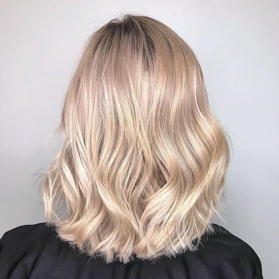 Image of the back of a woman's bob cut with creamy powdered blonde hair color styled in soft waves.