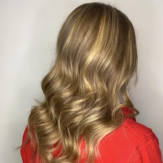 Image of the back of a woman's head with powdered bronde hair color styled in loose waves.