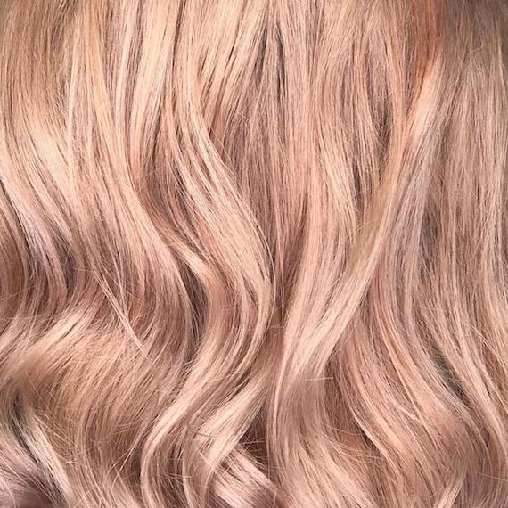 Close-up image of soft blush powdered hair color, showing hair texture styled in loose waves.