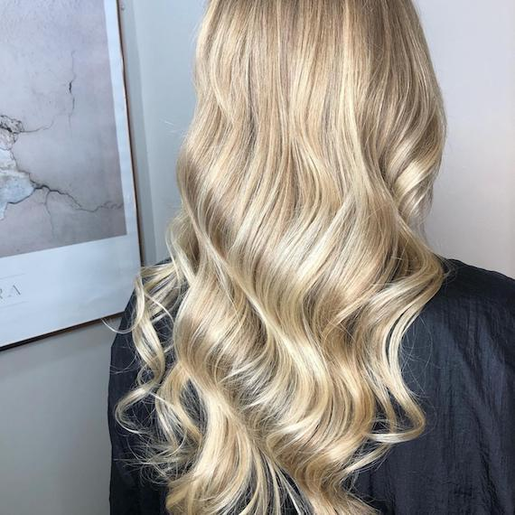 Image of the back of a woman's head with long hair, wearing powdered blonde balayage color styled in tonged waves.