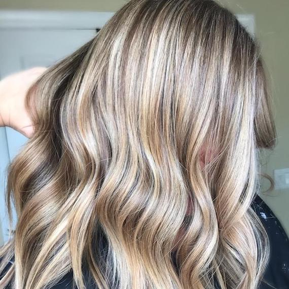 Image of the side of a woman's hair wearing powdered blonde babylights styled in loose waves.