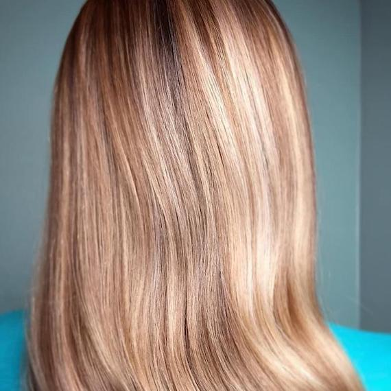 Close-up image of the back of a woman's head with powdered blonde highlights on a dark blonde base.