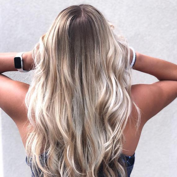 Image of the back of a woman's head wearing powdered blonde ombre hair color.