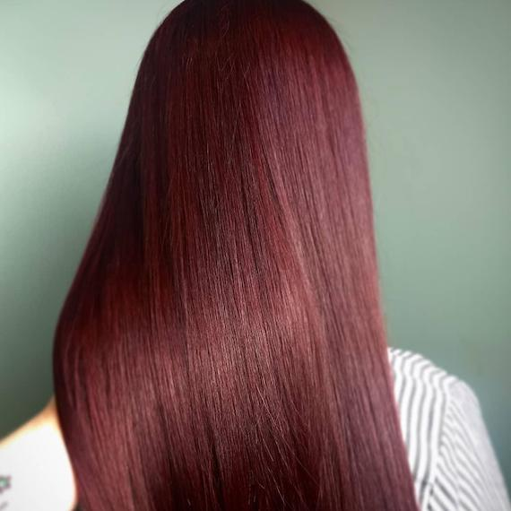 Photo of long, straight, black cherry hair, created using Wella Professionals.