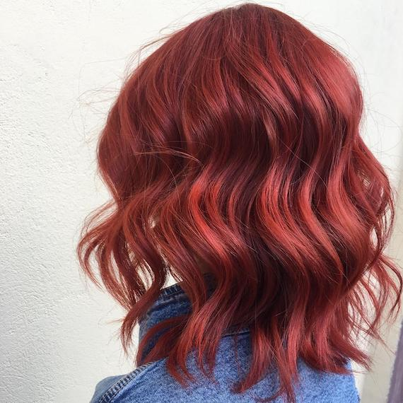 Photo of a wavy, cherry red bob haircut, created using Wella Professionals.