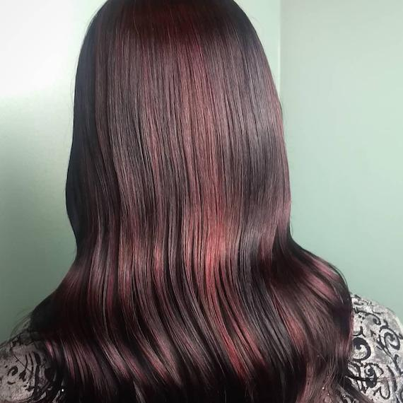 Photo of long, wavy, cherry cola hair, created using Wella Professionals.