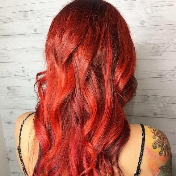 Photo of long, wavy, cherry red hair, created using Wella Professionals.