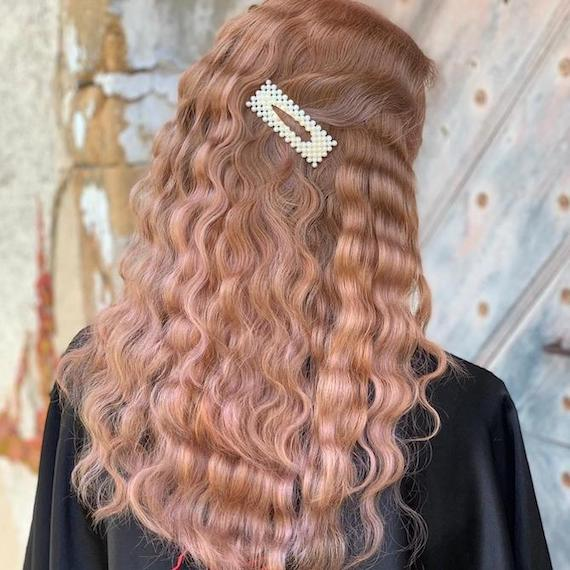 Back of a woman's hair with tight waves and a pearl barrette, created using Wella Professionals.