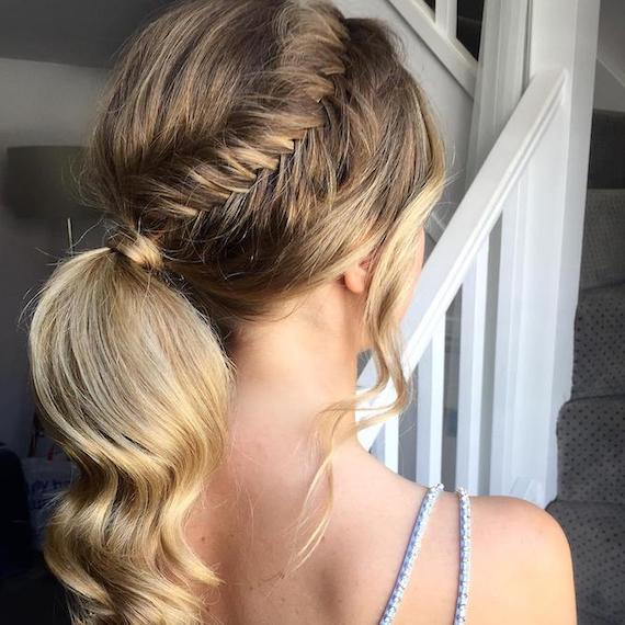 Photo of the back of a woman's head with hair styled in a low ponytail and fishtail braid, created using Wella Professionals.