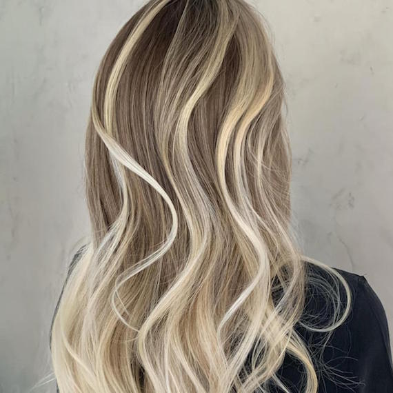 Back of woman's head with chunky, platinum blonde highlights through long, wavy hair, created using Wella Professionals.