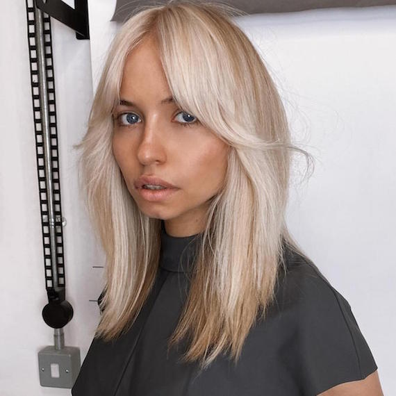 Woman with chunky thick blonde highlights and grown-out bangs, created using Wella Professionals.