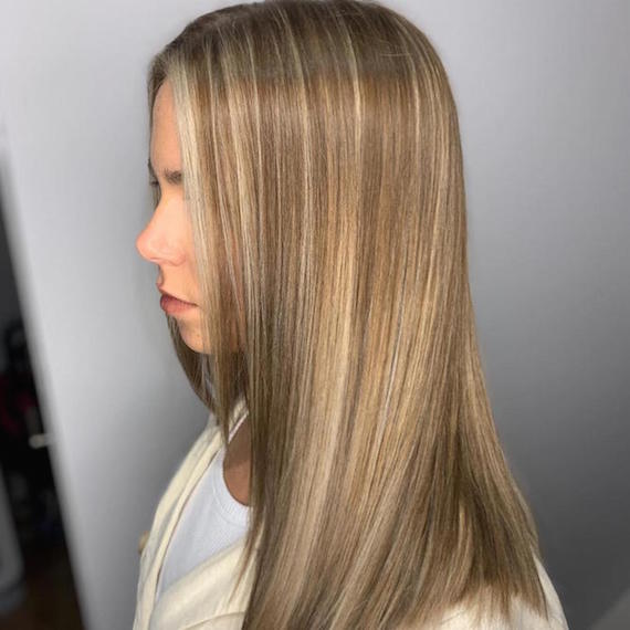 Woman with chunky lowlights through blonde hair, created using Wella Professionals.