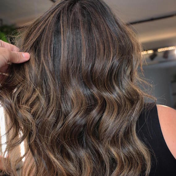 Back of woman's head with chunky, chocolate brown highlights through long, wavy hair, created using Wella Professionals.