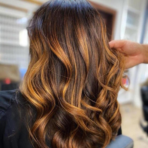Back of woman's head with chunky, copper highlights through long, loosely curled hair, created using Wella Professionals.