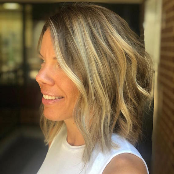 Side profile of woman with chunky highlights and lowlights through a blonde bob, created using Wella Professionals.