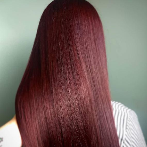 Photo of the back of a woman's head with longer, straight, shiny, maghogany hair, created using Wella Professionals.