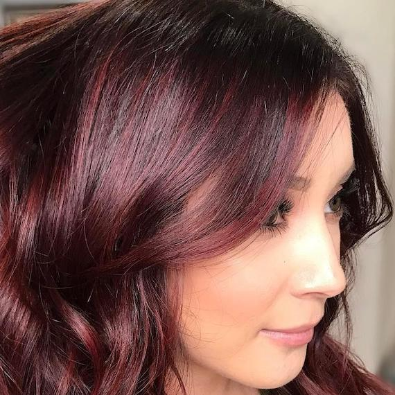 Photo of woman with wavy, dark mahogany hair, created using Wella Professionals.