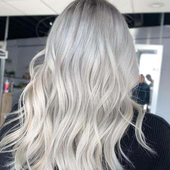 Back of woman's head with long, wavy, silver hair, created using Wella Professionals.