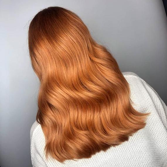 Back of woman's head with long, wavy, copper red hair, created using Wella Professionals.