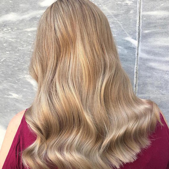 Back of woman's head with long, wavy, creamy blonde hair, created using Wella Professionals.