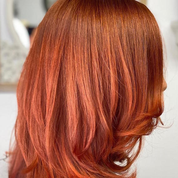 Side profile of woman with mid-length, copper red hair color, created using Wella Professionals.