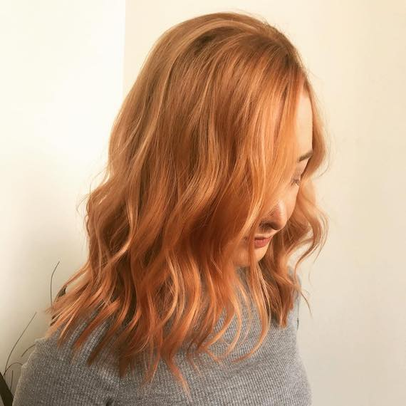 Side profile of woman with coral copper hair, created using Wella Professionals.