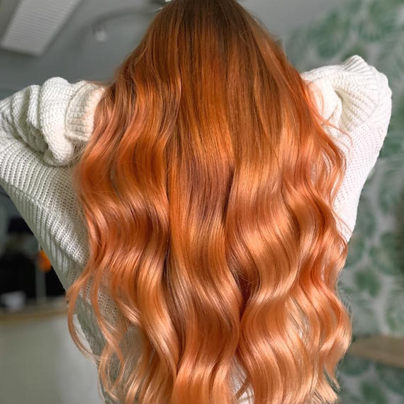 Back of woman's head with long, wavy, copper orange hair color, created using Wella Professionals.