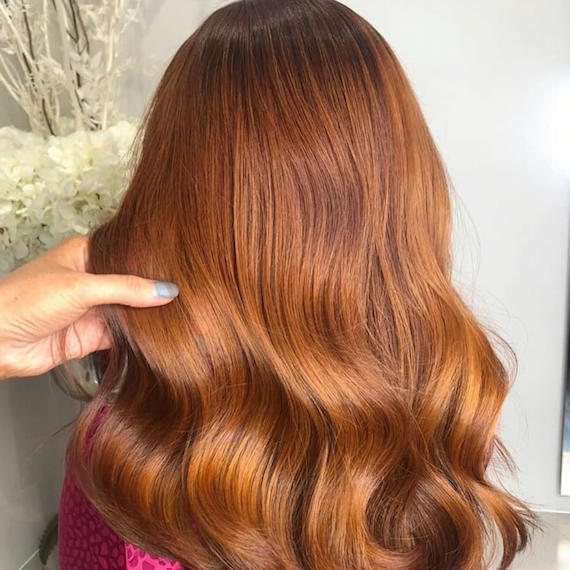 Back of woman's head with mid-length, wavy, ginger copper hair color, created using Wella Professionals.