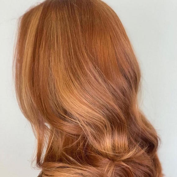 Side profile of woman with wavy, blonde copper hair, created using Wella Professionals.